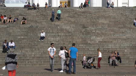 senate square : HELSINKI, FINLAND - AUGUST 31, 2016: Many young people, students and tourists sit on the steps in front of the Cathedral on the Senate Square in Helsinki. Tame lapse. Stock Footage