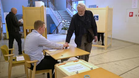 előny : HELSINKI, FINLAND - 09 APRIL, 2017: People casting a vote into the ballot box during municipal elections.
