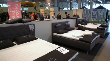мебель : HELSINKI, FINLAND - APRIL 07, 2017: Buyers are experiencing a new orthopedic bed with remote control. Annual Fair Spring Garden at the Expocenter of Messukeskus. Стоковые видеозаписи