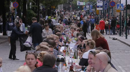 all ages : HELSINKI, FINLAND - JUNE 12, 2016: A lot of people eating and drinking at the same table. Traditional common table for everyone in honor of the Day of the City in the center of Helsinki. Time Lapse. Stock Footage