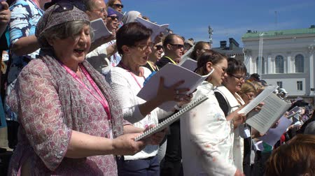 senate square : HELSINKI, FINLAND - MAY 19, 2017: Huge choir singing on the steps of the Cathedral. Rehearsal for the big choir at the Senate square on the eve of the church music festival Sana soi Stadissa .
