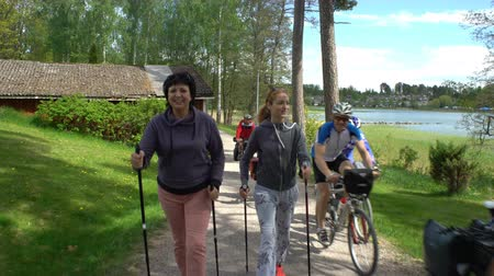 all ages : Nordic walking outdoor activity for all ages. Two active women working out in the Park. Tracking shot. Stock Footage