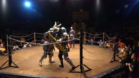reencenação : MOSCOW, RUSSIA - APR 12, 2016: Two Medieval Knights Fighting In The Arena With Clubs And Shields. Great Knights tournament Valor and Honor .