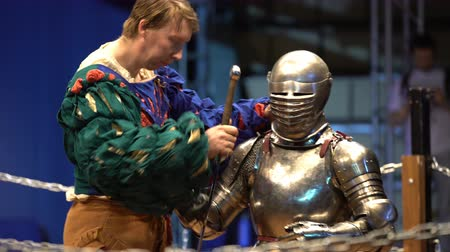reencenação : MOSCOW, RUSSIA - APR 12, 2016: A Squire Helps A Knight To Wear A Helmet Before A Fight. Great Knights tournament Valor and Honor .