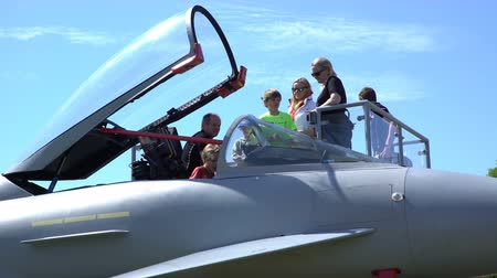 aircrew : HELSINKI, FINLAND - JUNE 09, 2017: Adults and children visiting the cockpit of a military supersonic fighter during THE KAIVOPUISTO AIR SHOW 2017.