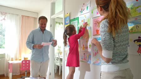 crayon : Happy family. Little girl and her parents hang childrens drawings on the wall in the nursery. Slow motion. Stock Footage