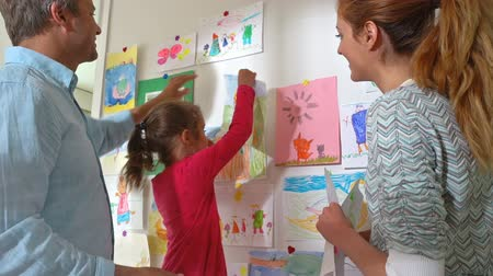 mateřská škola : Happy family. Little girl and her parents hang childrens drawings on the wall in the nursery. Slow motion. Dostupné videozáznamy