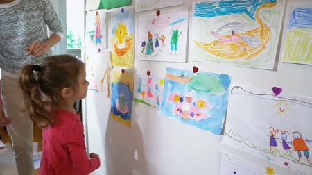 mateřská škola : Little cute girl and her mother hang childrens drawings on the wall in the nursery. Slow motion.