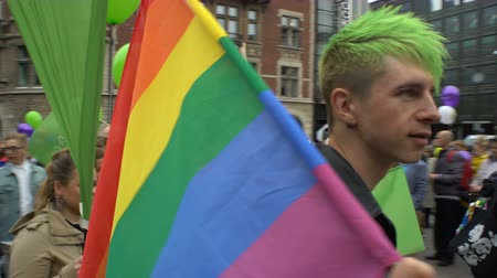 gurur : HELSINKI, FINLAND - JULY 01, 2017: Young man with Rainbow flag. Thousands of people in solidarity during a Gay pride parade on the streets of Helsinki.