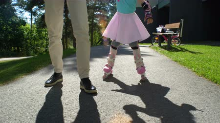 learning to walk : First skating. Young Mum Helps her Little Daughter to Skate on Roller Skates