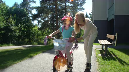 öğrenme : First cycling. Mother teaches her daughter to ride a bicycle.