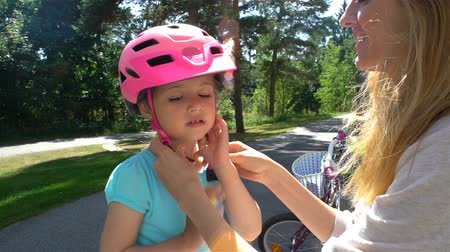 güçlü : Caring young mother puts safety helmet on his little daughters head. Slow motion