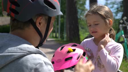 kolo : Caring Dad puts safety helmet on his little daughters head. Slow motion