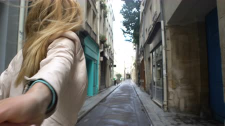 descobrir : Follow me. Young Woman Leading a Man to the Adventure in an Unfamiliar European City.