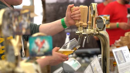 renowned : HELSINKI, FINLAND - JULY 29, 2017: Barmen pour beer from beer taps. Beer Fair in the Railway Square in Helsinki