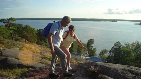 aventura : Elderly active couple climbing on the rock and admiring the sunrise, the sunset. Scandinavian landscape with sea and pine trees. Slow Motion
