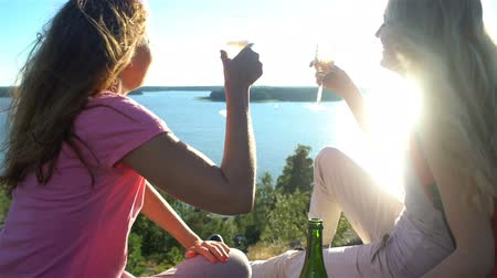 eufória : Happy Female Couple Drinking Champagne on a High Rock in the Sunshine. Nordic landscape with pine trees, cliffs and sea.