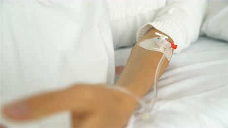 saline drip : A young female patient in a hospital ward with a drip