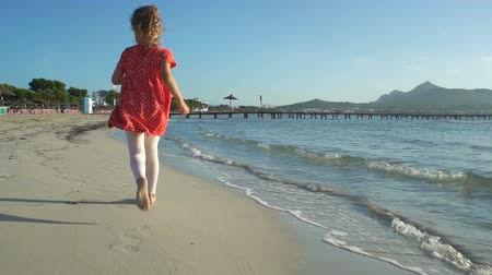 barefooted : Little girl in bright red dress running on the beach barefoot
