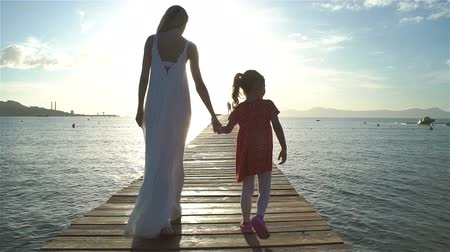 atracação : Young woman with her Little daughter walking on a wooden sea pier towards the rising sun