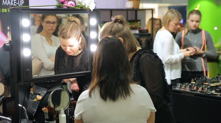 alışveriş : HELSINKI, FINLAND - OCTOBER 20, 2017: Makeup artist applies make-up to the young woman. Fair I LOVE ME - Beauty, Health, Naturally, Fashion and Jewel Watch at Messukeskus Expo Centre Stok Video