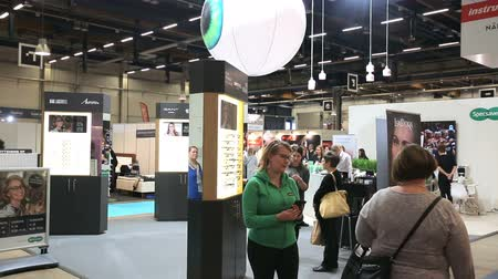 okulista : HELSINKI, FINLAND - OCTOBER 20, 2017: Buyers choosing new optical glasses in optician shop. Fair I LOVE ME - Beauty, Health, Naturally, Fashion and Jewel Watch at Messukeskus Expo Centre
