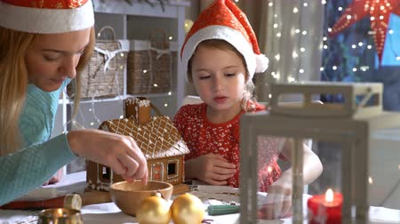 decorating : Young mother and adorable daughter in red hat building gingerbread house together. Beautiful decorated room with lights and Christmas tree, table with candles and lanterns. Happy family celebrating holiday.
