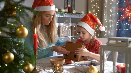 pan di zenzero : Young mother and adorable daughter in red hat building gingerbread house together. Beautiful decorated room with lights and Christmas tree, table with candles and lanterns. Happy family celebrating holiday.