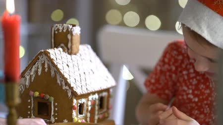 Санта : Young mother and adorable daughter in red hat building gingerbread house together. Beautiful decorated room with lights and Christmas tree, table with candles and lanterns. Happy family celebrating holiday. Slow Motion