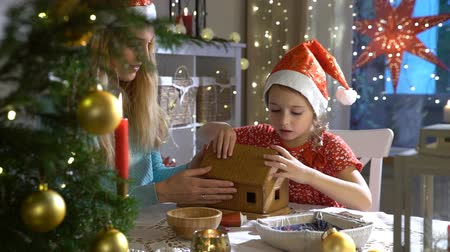pan di zenzero : Young mother and adorable daughter in red hat building gingerbread house together. Beautiful decorated room with lights and Christmas tree, table with candles and lanterns. Happy family celebrating holiday. Slow Motion
