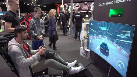 gry komputerowe : HELSINKI, FINLAND - NOVEMBER 3, 2017: Young men playing new games from XBOX ONE X car race with the wheel. Newest gadgets on GAME EXPO in the exhibition center Messukeskus.