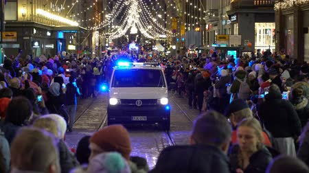squad car : HELSINKI, FINLAND - NOVEMBER 26, 2017: Police car with flashing lights slowly moving among the festive crowd Stock Footage