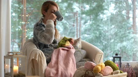 sill : Cozy winter lifestyle. Young woman knitting warm wool sweater in the sitting room against snow landscape from outside. Slow Motion