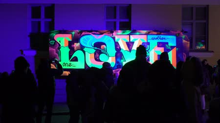 lux : HELSINKI, FINLAND - MAY 07, 2018: Fluorescent graffiti LOVE on the wall during the public Festival of Light LUX.