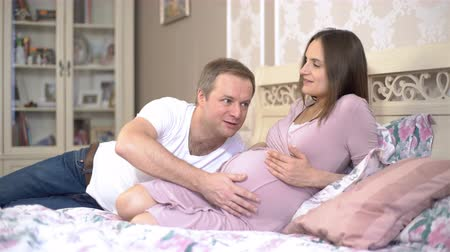születés előtti : The man listening and kissing the belly of his pregnant wife. 4K Stock mozgókép