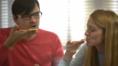 iştah : Young attractive woman and handsome man eating hot delicious pizza. Stok Video