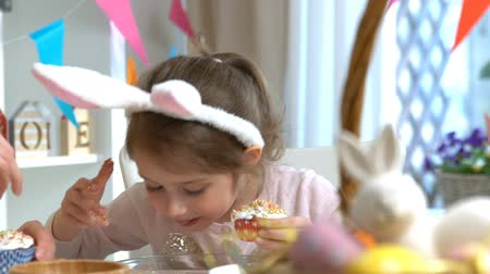 rabbit ears : Young mother and her cute little daughter wearing funny rabbit ears are cooking Easter cupcakes sitting at a festive table with basket, eggs and Bunny. Slow Motion