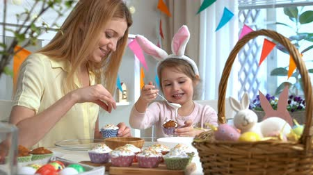 koszyk wielkanocny : Young mother and her cute little daughter wearing funny rabbit ears are cooking Easter cupcakes sitting at a festive table with basket, eggs and Bunny. Slow Motion