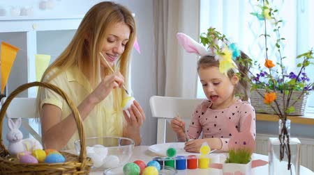 buona pasqua : Happy Easter! Young mother and her cute little daughter wearing funny rabbit ears are coloring easter eggs sitting at a festive table with basket and Bunny. Slow Motion