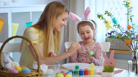 koszyk wielkanocny : Happy Easter! Young mother and her cute little daughter wearing funny rabbit ears are coloring easter eggs sitting at a festive table with basket and Bunny. Slow Motion