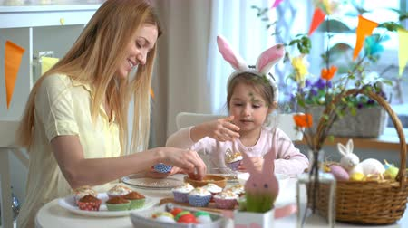 koszyk wielkanocny : Young mother and her cute little daughter wearing funny rabbit ears are cooking Easter cupcakes sitting at a festive table with basket, eggs and Bunny Wideo