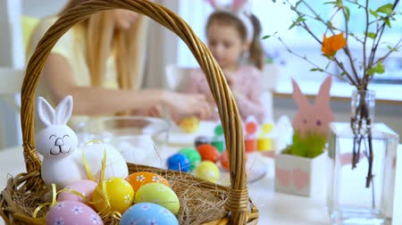 koszyk wielkanocny : Happy Easter! Young mother and her cute little daughter wearing funny rabbit ears are coloring easter eggs sitting at a festive table with basket and Bunny