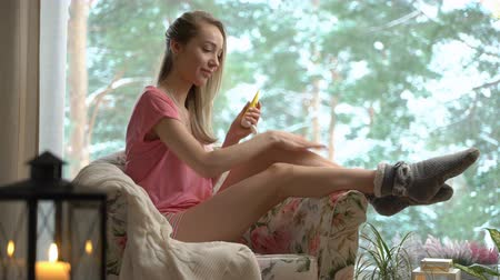 underwear : Young woman body care in cozy living room. Beautiful girl applying cream on her legs skin sitting in the chair by the window with winter landscape Stock Footage