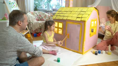 ипотека : Father gives happy little girl a toy key to her new cardboard house.