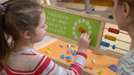 abacus : Early childhood development. Little girl learning time with clock toy at home. Play and learn Stock Footage