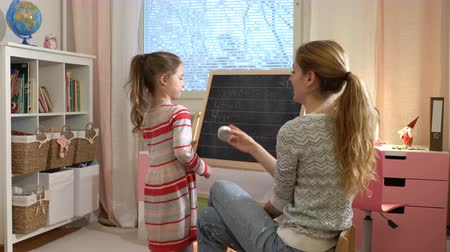 aritmética : Early childhood development. Young mother explaining arithmetic to cute little daughter with blackboard at home