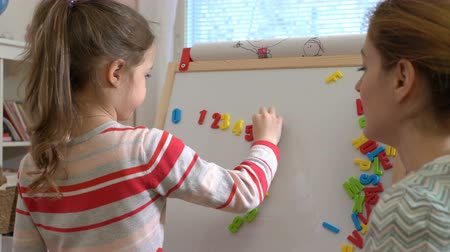 soma : Early childhood development. Young mother explaining arithmetic to cute little daughter with special desk at home