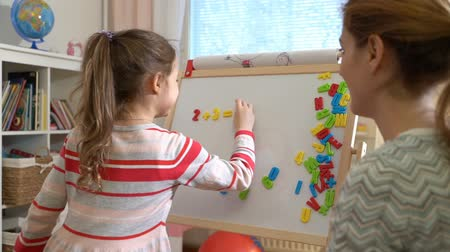 aritmetický : Early childhood development. Young mother explaining arithmetic to cute little daughter with special desk at home. Play and learn. Slow motion
