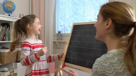 számvitel : Early childhood development. Young mother explaining arithmetic to cute little daughter with blackboard at home. Play and learn. Slow motion