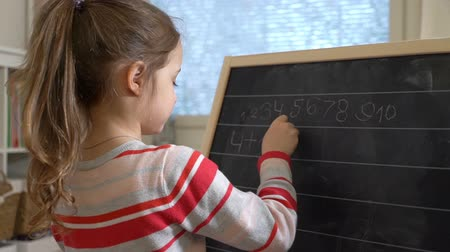 aritmetický : Early childhood development. Young mother explaining arithmetic to cute little daughter with blackboard at home. Play and learn. Slow motion